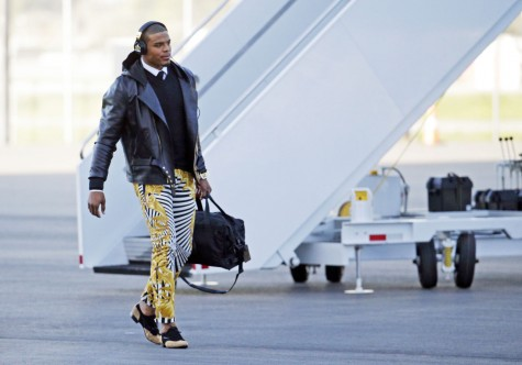 FILE - In this Jan. 31, 2016 file photo, Carolina Panthers quarterback Cam Newton gets off the plane at the Mineta San Jose International Airport in San Jose, Calif.  The Panthers play the Denver Broncos on Sunday, Feb. 7, 2015, in Super Bowl 50. Newton was snapped Sunday in the zebra stripe, gold swirl rocker pants immediately setting social media and TV talking heads into a frenzy. (AP Photo/Charlie Riedel, File)