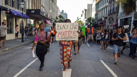 A woman holds a sign in the streets of downtown Charleston