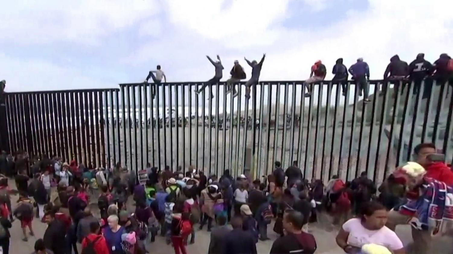 Migrants attempt to cross tall fences at the U.S.-Mexico border (Image courtesy of NBC).