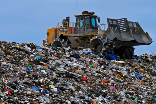 An excavator on top of a landfill.