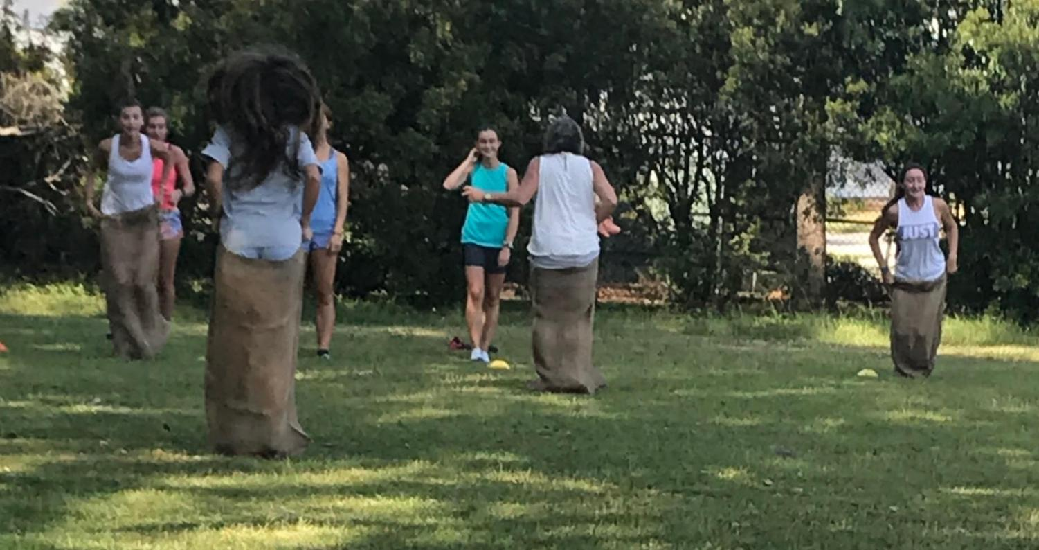 The team is seen here partaking in a sack race to promote fitness and fun.