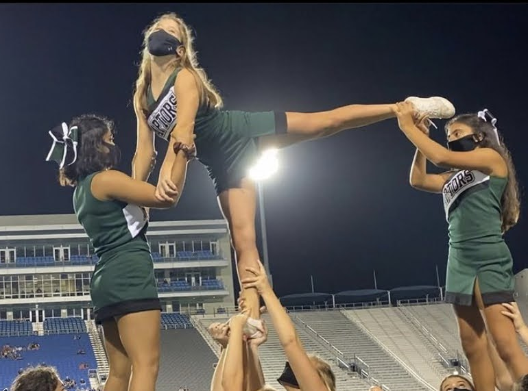 Pyramid stunting at a game  (Flyers, left to right: Disha Qanungo, Chandler Grace Ghegan, Summer DeSouza)